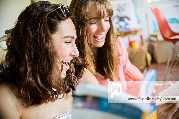 Zwei junge Freundinnen beim Stöbern und Lachen über Bücher