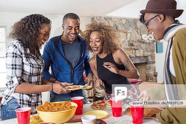 Vier erwachsene Freunde essen Partyessen in der Küche