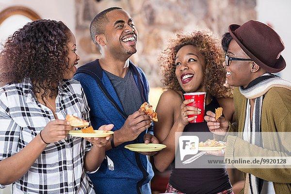 Vier erwachsene Freunde lachen und essen Partyessen in der Küche