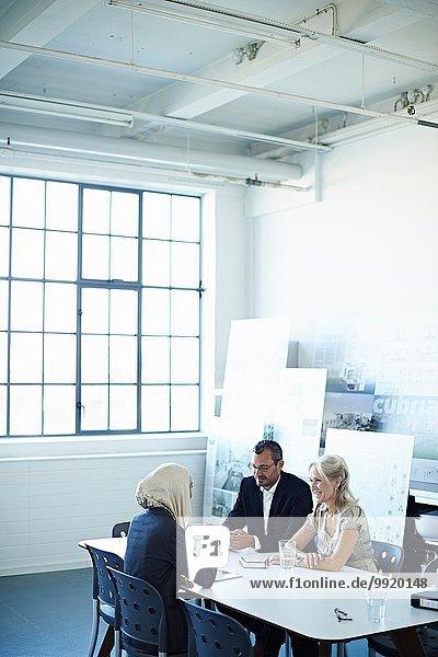 Zwei Geschäftsfrauen und ein Mann im Bürogespräch