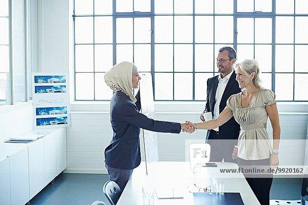 Junge Geschäftsfrau beim Händeschütteln mit Geschäftsfrau im Amt
