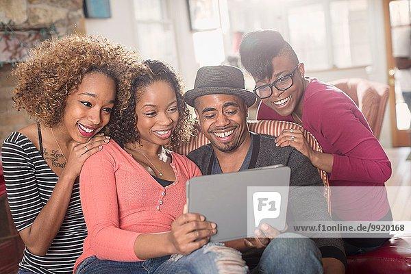 Vier erwachsene Freunde sitzen auf dem Sofa und schauen sich das digitale Tablett an.