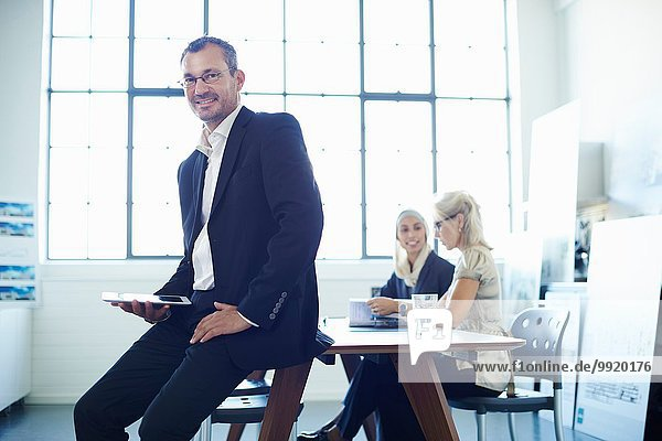 Porträt eines reifen Geschäftsmannes  der auf dem Schreibtisch sitzt.