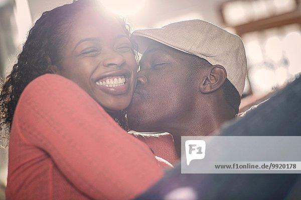 Mittlerer Erwachsener Mann  der seine Freundin auf die Wange küsst.