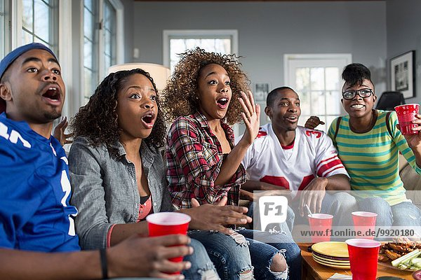 Fünf erwachsene Freunde keuchen  während sie vom Sofa aus fernsehen.
