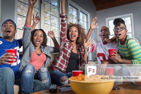 Fünf erwachsene Freunde feiern  während sie vom Sofa aus fernsehen.