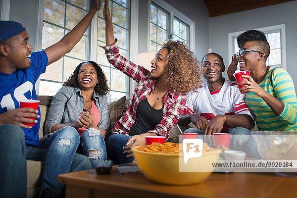 Fünf erwachsene Freunde feiern mit High Five  während sie vom Sofa aus fernsehen.