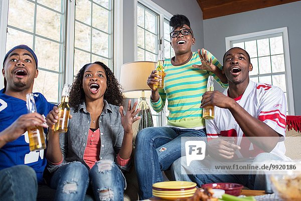 Vier erwachsene Freunde keuchen mit offenem Mund  während sie vom Sofa aus fernsehen.
