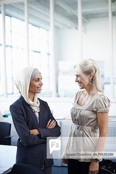 Junge und reife Geschäftsfrauen chatten im Büro