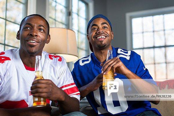 Zwei männliche Freunde trinken Flaschenbier  während sie vom Sofa aus fernsehen.