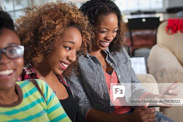 Drei Freundinnen beim Lesen von Smartphone-Texten auf dem Wohnzimmersofa