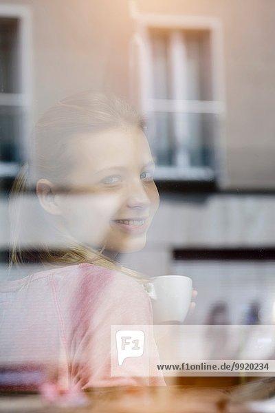 Porträt einer jungen Frau  die Kaffee trinkt und durchs Caféfenster schaut