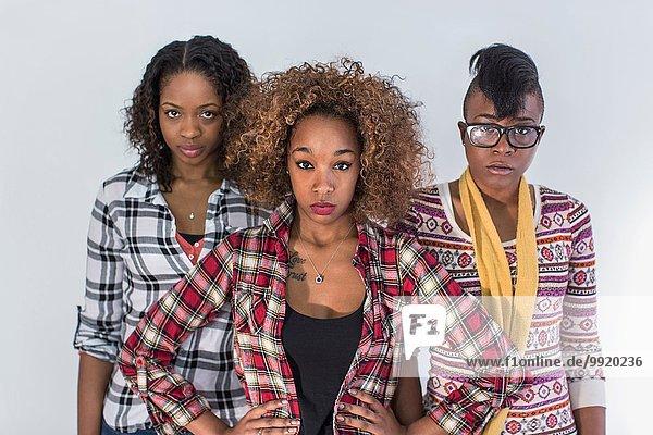 Studio-Porträt von drei ernsthaft starrenden jungen Frauen