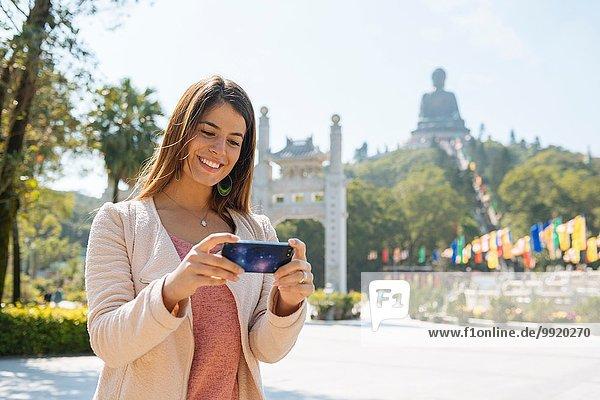 Junge Touristin beim Betrachten von Smartphone-Fotos vor Tian Tan Buddha  Po Lin Kloster  Lantau Island  Hongkong  China
