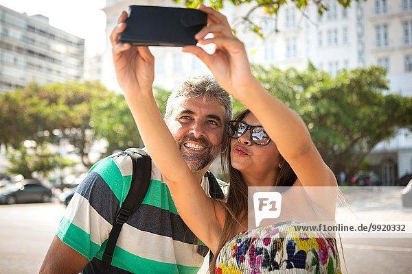 Junge Frau und reifer Mann mit Smartphone Selfie  Copacabana  Rio De Janeiro  Brasilien