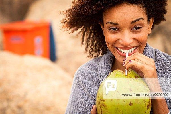 Porträt einer jungen Frau  die am Strand von Ipanema  Rio De Janeiro  Brasilien  Kokosmilch trinkt.