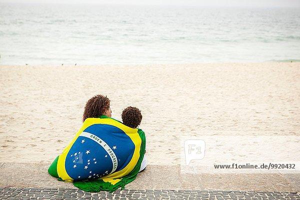 Rückansicht von Mutter und Sohn in brasilianischer Flagge am Strand von Ipanema  Rio De Janeiro  Brasilien