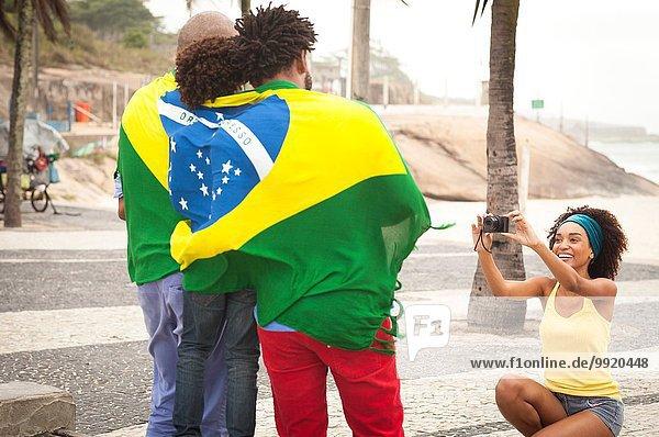 Junge Mutter fotografiert Familie in brasilianischer Flagge am Strand von Ipanema  Rio De Janeiro  Brasilien.