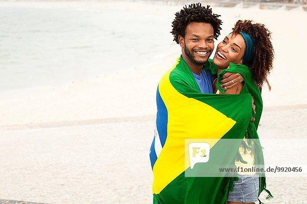 Paarumarmung in brasilianischer Flagge am Strand von Ipanema  Rio De Janeiro  Brasilien