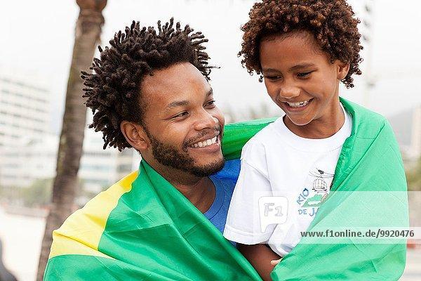 Vater und Sohn mit brasilianischer Flagge am Strand von Ipanema  Rio De Janeiro  Brasilien