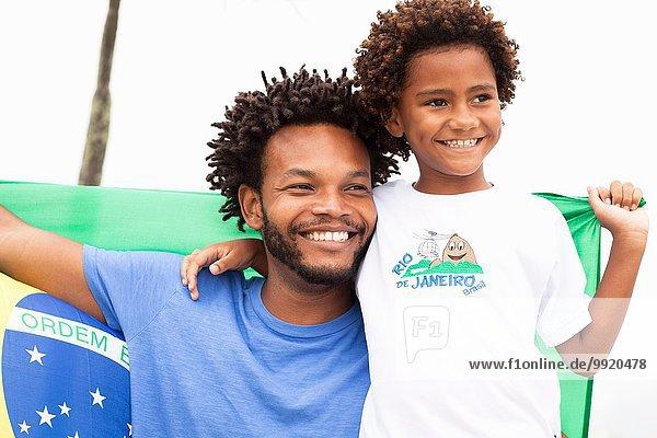 Vater und Sohn halten die brasilianische Flagge am Strand von Ipanema  Rio De Janeiro  Brasilien.