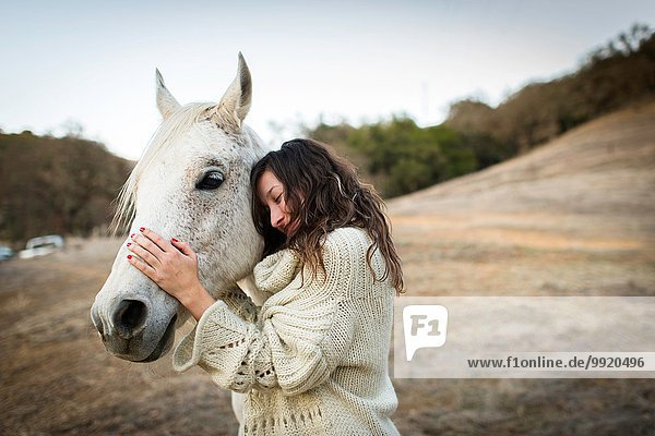 Junge Frau anlehnend und streichelndes weißes Pferd im Feld