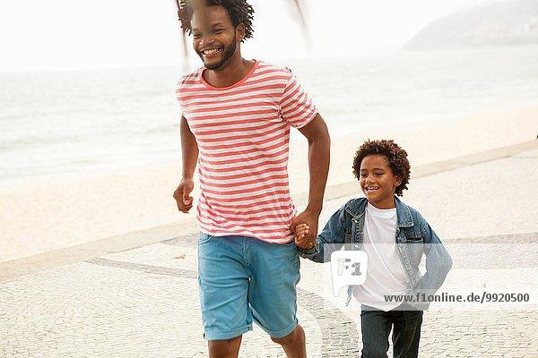 Vater und Sohn laufen Hand in Hand  Strand von Ipanema  Rio De Janeiro  Brasilien
