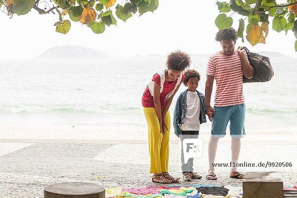 Paar und Sohn wählen Kleidung vom Bürgersteig  Ipanema Strand  Rio De Janeiro  Brasilien