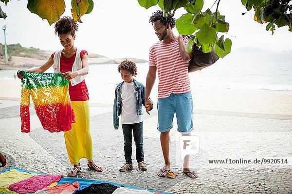 Pärchen und Sohn wählen Pullover vom Bürgersteig  Ipanema Strand  Rio De Janeiro  Brasilien