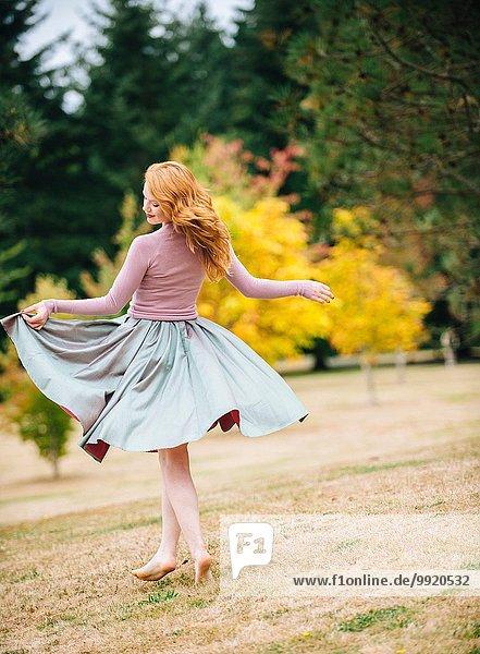 Junge Tänzerin beim Drehen und Heben des Rockes im Park