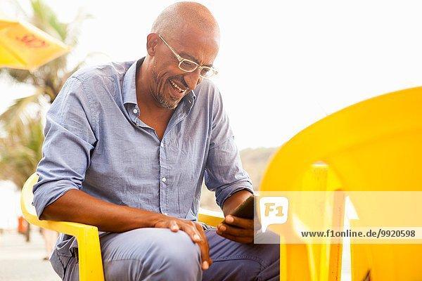 Reifer Mann beim Lesen von Smartphone-Texten an der Bar am Strand von Ipanema  Rio De Janeiro  Brasilien