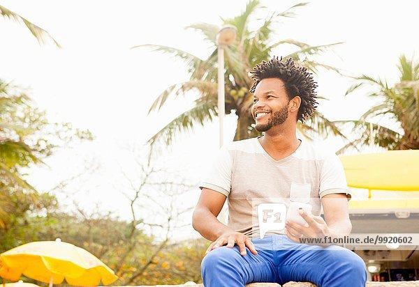 Mittlerer Erwachsener Mann  der an der Wand sitzt und ein Smartphone benutzt  Strand von Ipanema  Rio De Janeiro  Brasilien