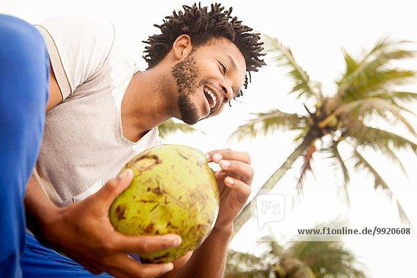 Tiefblick auf einen erwachsenen Mann  der Kokosmilch trinkt  Strand von Ipanema  Rio De Janeiro  Brasilien