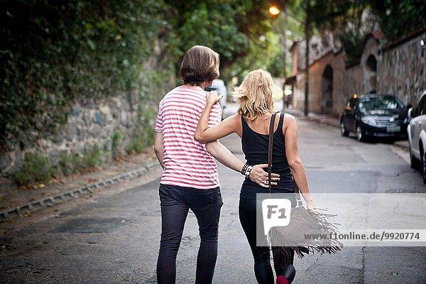 Rückansicht des jungen Paares auf der Vorstadtstraße