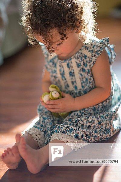 Junges Mädchen  auf dem Boden sitzend  mit Spielzeug spielend