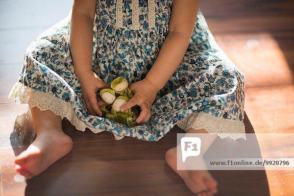Junges Mädchen  auf dem Boden sitzend  mit Spielzeug spielend  niedrige Sektion