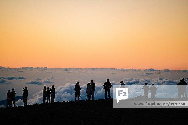 Reihe von silhouettierten Touristen oben bei Sonnenuntergang,  Haleakala Nationalpark,  Maui,  Hawaii