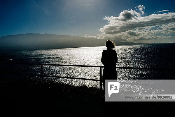 Silhouetted senior woman looking out to sea  Maui  Hawaii