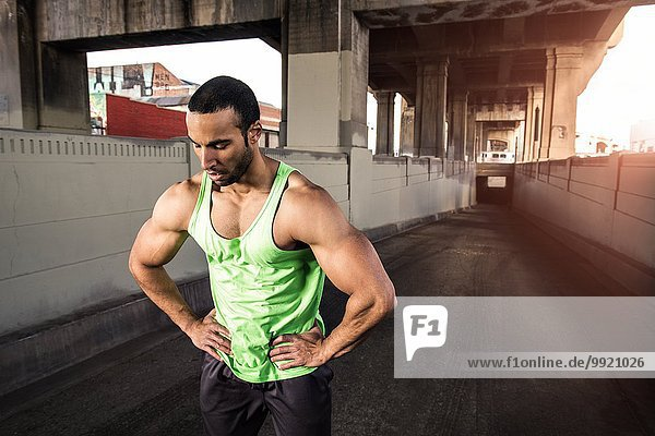 Muskulöser männlicher Läufer bei einer Pause unter der Stadtbrücke