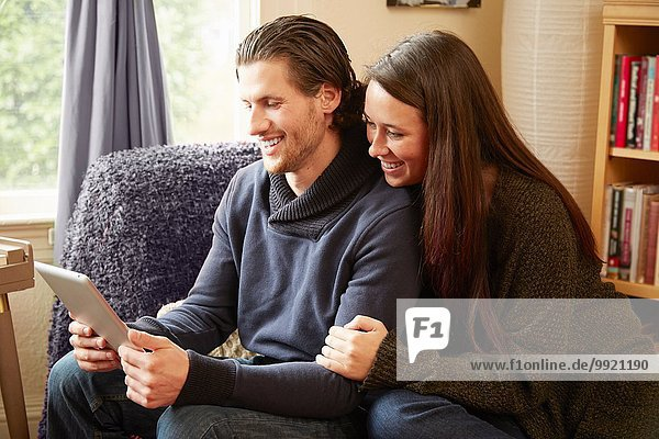Young couple browsing digital tablet in living room
