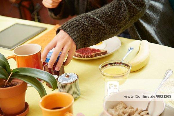 Schnappschuss von jungen Frauenhänden mit Marmeladenglas am Frühstückstisch