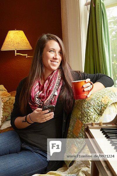 Junge Frau liegt auf dem Sofa und schaut aus dem Fenster  während sie Kaffee trinkt.