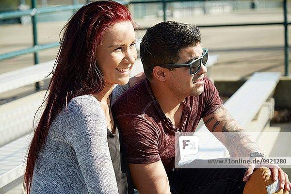 Junges Paar schaut von der Parkbank aus zu