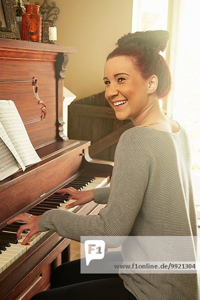 Junge Frau beim Klavierspielen im Wohnzimmer