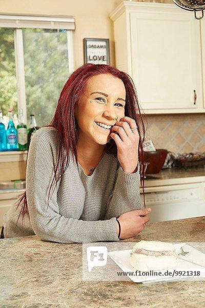 Porträt einer jungen Frau  die sich gegen die Küchenzeile lehnt.