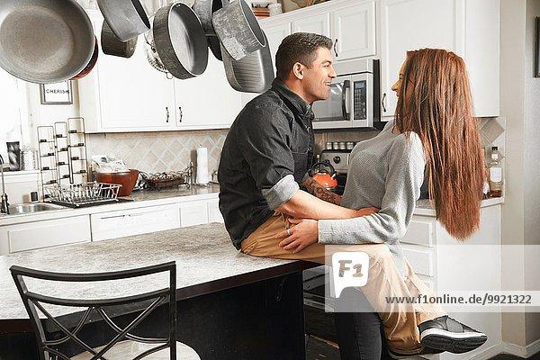 Junges Paar umarmt sich an der Küchentheke