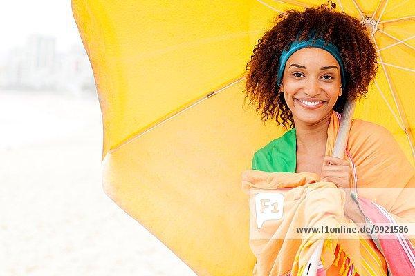 Junge Frau posiert mit Regenschirm am Strand