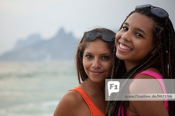 Porträt von zwei lächelnden jungen Frauen am Strand von Ipanema  Rio De Janeiro  Brasilien