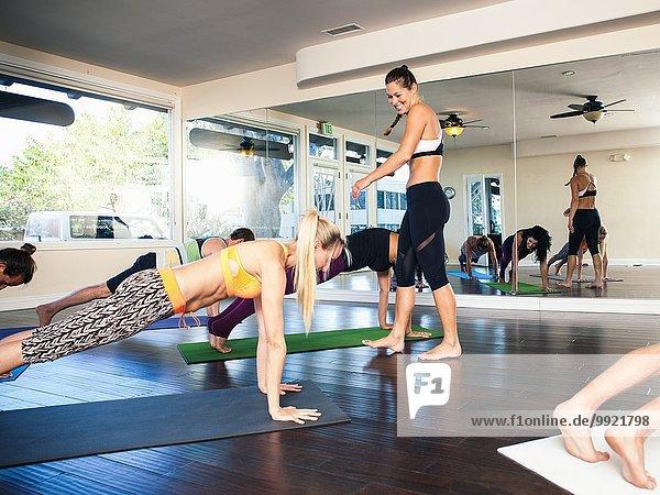 Yogalehrerin im Unterricht mit erwachsener Frau