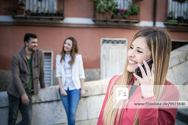Young woman with friends talking on smartphone  Cagliari  Sardinia  Italy